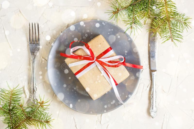 Christmas table setting with grey plate, gift box and silverware on light background, Fir tree branch royalty free stock photos