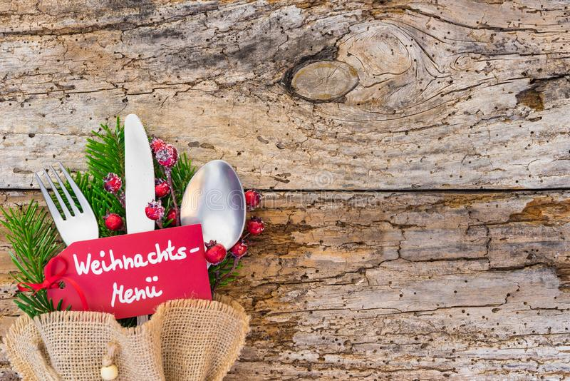 Christmas table setting with label an german text, Weihnachts-Menue, means christmas menu, on rustic wooden table royalty free stock photography