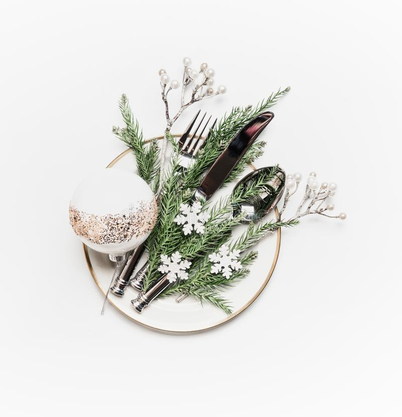 Christmas table setting . Plate with fir branches , cutlery and festive holiday decoration: ball and little snowflakes on white. Background, top view stock photos
