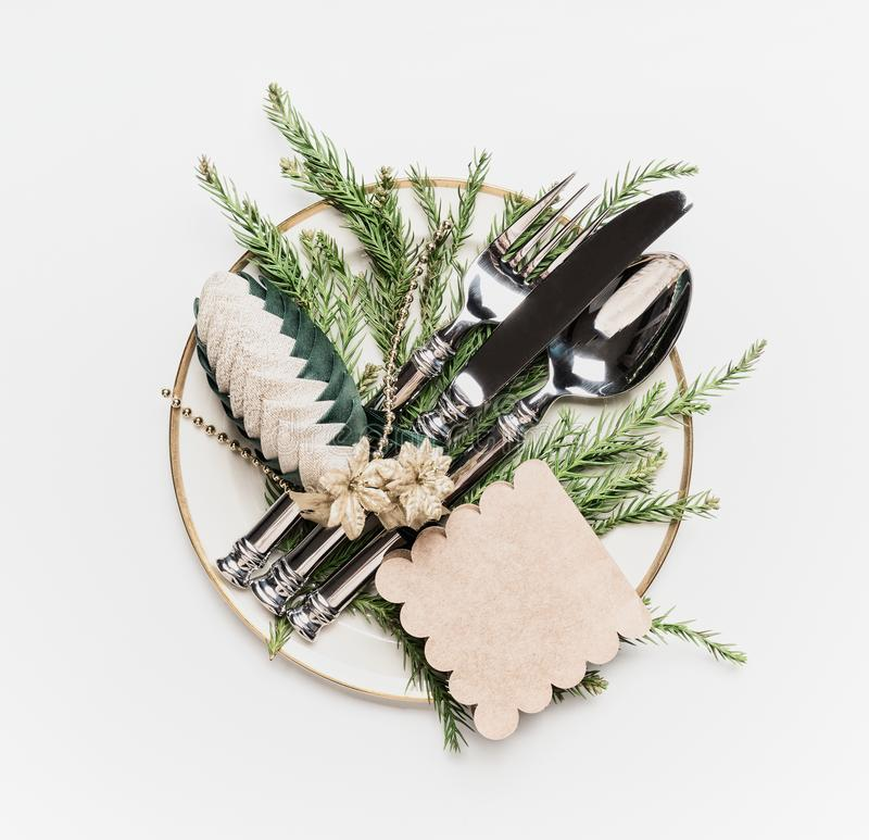 Christmas table setting . Plate with fir branches , cutlery and festive holiday decoration: pine cone and tag on white stock photography