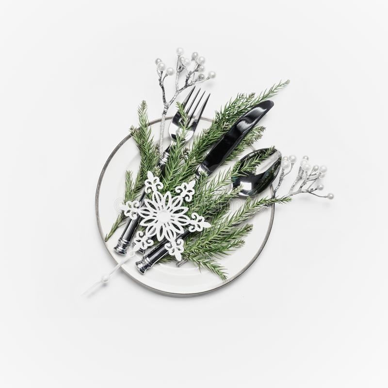 Christmas table setting . Plate with fir branches , cutlery and festive holiday decoration: silver twigs and snowflake on white royalty free stock photos