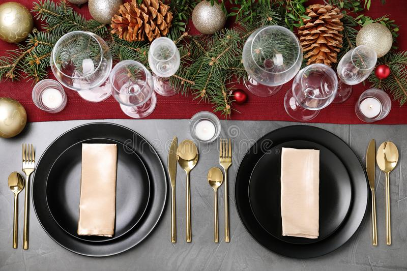 Christmas table setting with plates, cutlery, napkins and festive decor on grey background. Flat lay stock photo