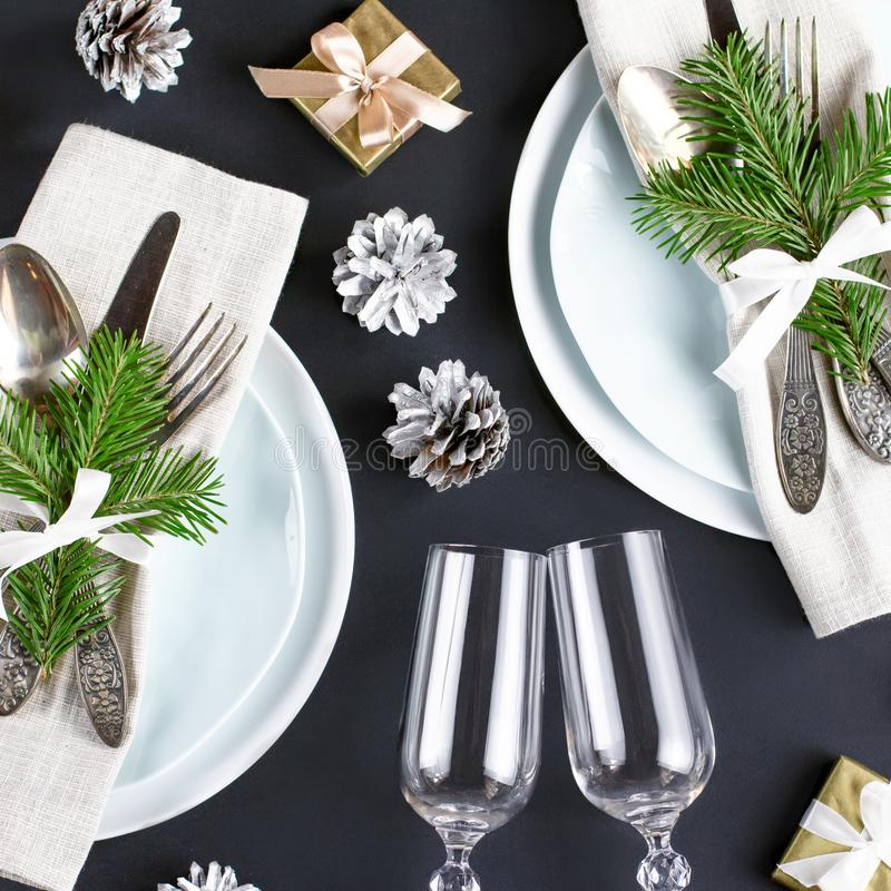 Christmas table setting with plates, silverware, gift box and decorations in black and gold colors. Top view stock photo
