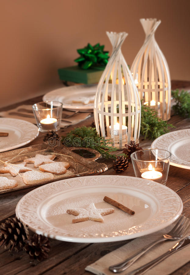 Christmas table setting, rustic style, natural decorations. Christmas table setting. Elegant white plates with cookies, natural pine tree branch, pinecones stock image