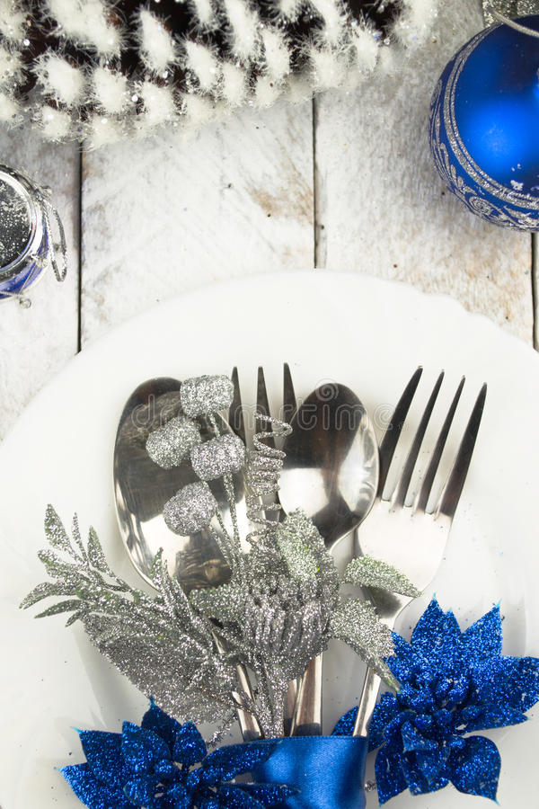 Christmas table setting in silver and blue tone on wooden table royalty free stock photo