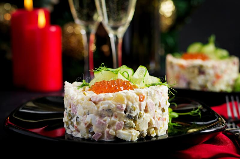 Christmas table setting. Traditional Russian salad `Olivier`. New Year salad. Festive salad stock photography