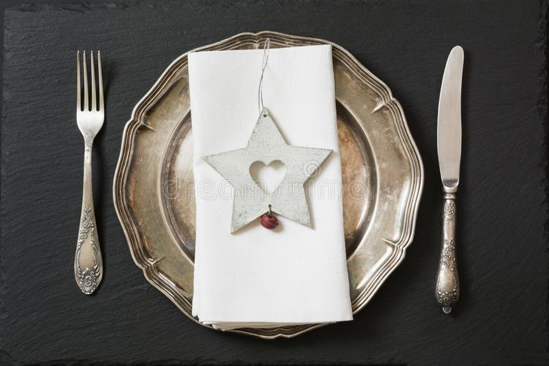 Christmas table setting with vintage dishware, silverware and star decorations. Top view. royalty free stock photo