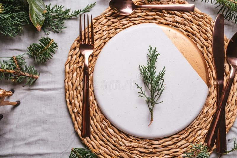 Christmas table settings with a wreath, pine branch and golden cutlery. From above, Holiday dinner royalty free stock image