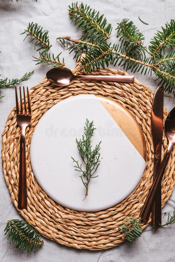Christmas table settings with a wreath, pine branch and golden cutlery. From above, Holiday dinner stock image
