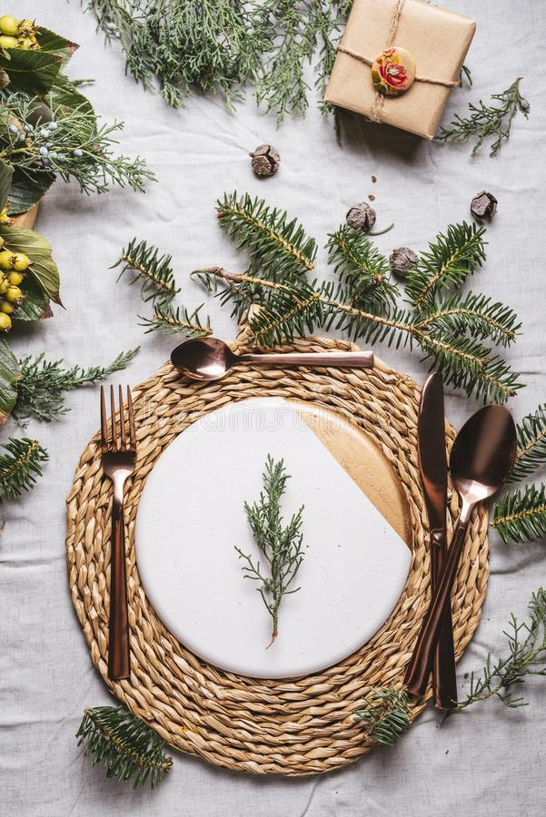 Christmas table settings with a wreath, pine branch and golden cutlery. From above, Holiday dinner stock photography
