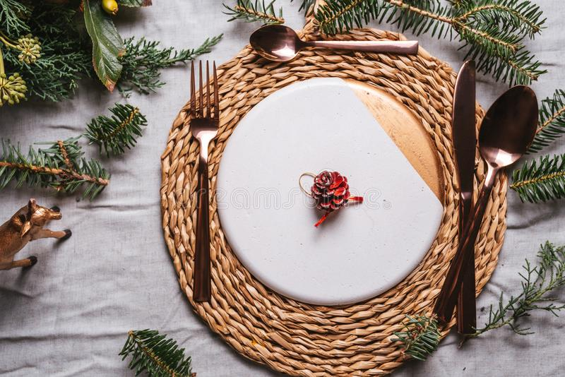 Christmas table settings with a wreath, pine branch and golden cutlery. From above, Holiday dinner royalty free stock images