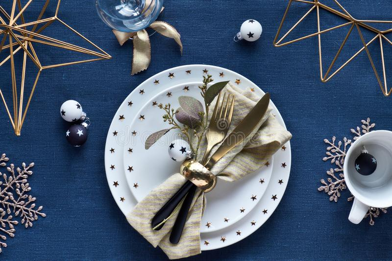 Christmas table setup with white plate and golden utensils and gilded decorations. White and black glass baubles with stars. Flat royalty free stock image