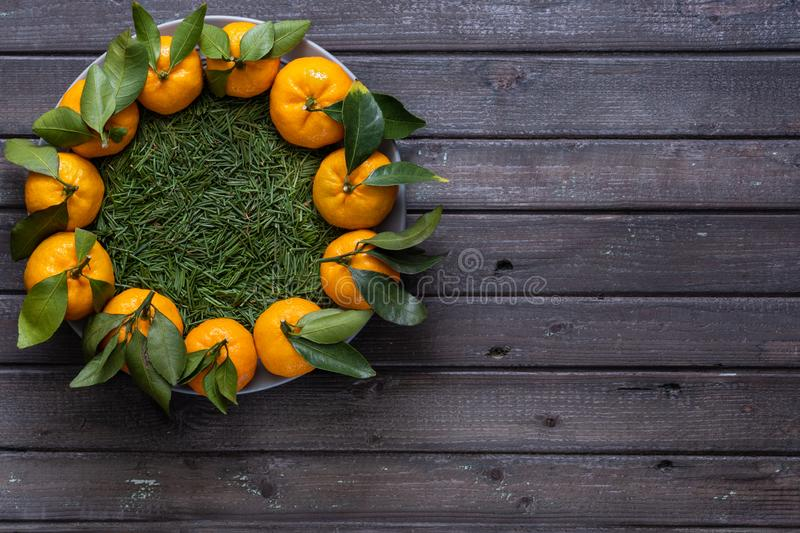 Christmas tangerines with leaves lie in a plate covered with conifer needles royalty free stock photo