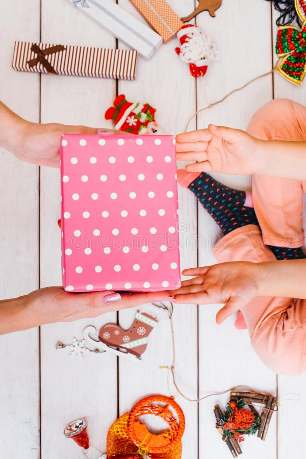 Christmas teamwork. Festive family help. Unrecognizable females wrapping gifts on wooden background top view, beauty tinsel. Presents decoration process royalty free stock photography