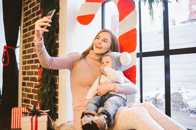 Christmas, technology and family concept, happy mother and little son taking selfie smartphone at home. Kid and mom make royalty free stock photography
