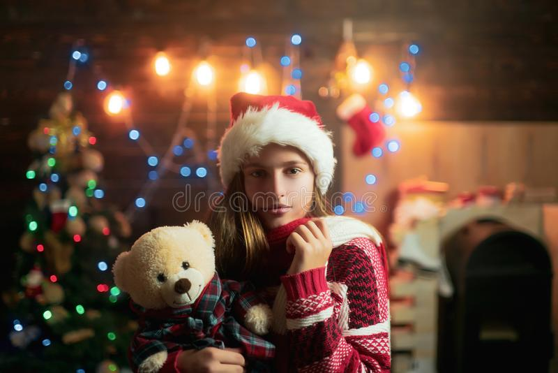 Christmas teenager. Cute little girl teenager is decorating the Christmas tree indoors. Happy little girl dressed in. Winter clothing think about Santa near stock images