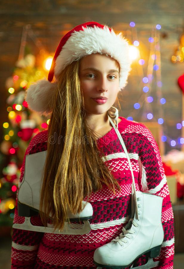 Christmas teenager. Merry Christmas and Happy Holidays. Smiling Little girl peeping from behind Christmas tree in living. Room. Cute little girl near Christmas stock photos