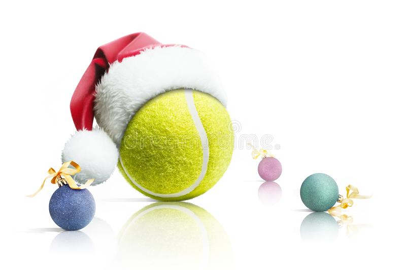 Christmas tennis. Tennis ball in Santa hat Christmas toys on white background. Isolated royalty free stock images