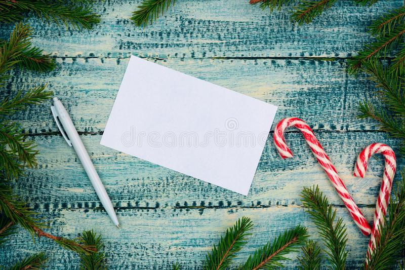 Christmas texture on a blue wooden background a piece of paper, a pen and candy canes royalty free stock photo