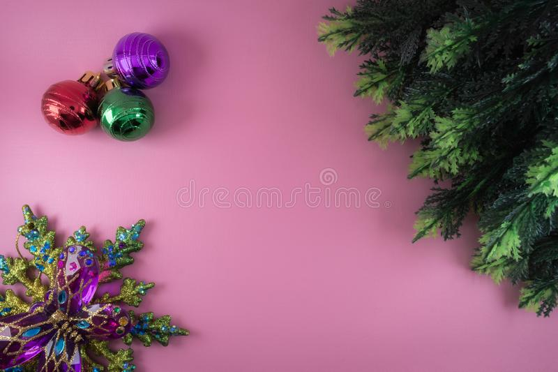 Christmas theme border or frame. made from plastic cypress leaves and colorful ornament in pink background. Christmas, theme, border, pink, background stock photos