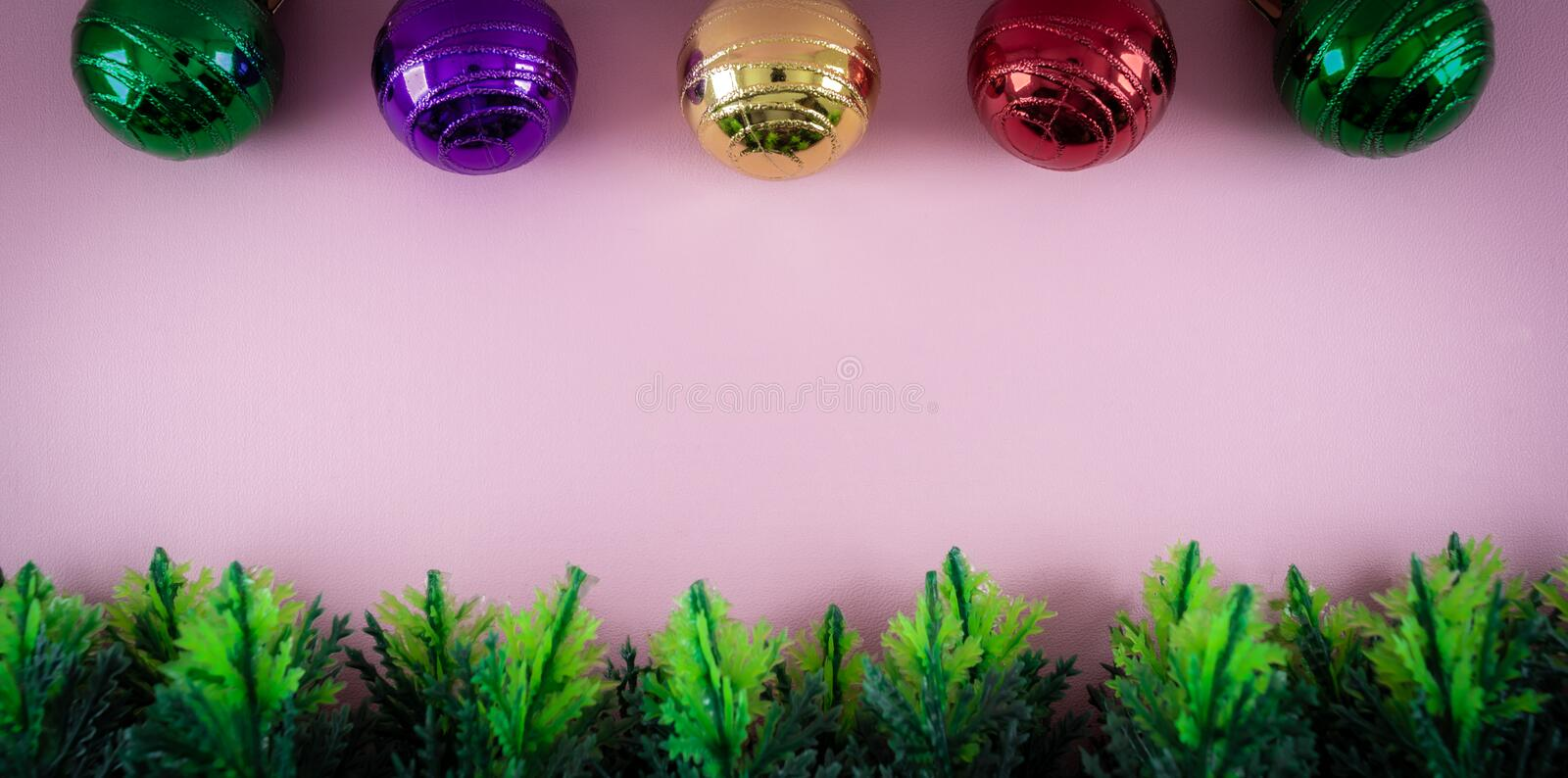 Christmas theme border or frame. made from plastic cypress leaves and colorful ornament in pink background. Christmas, theme, border, pink, background royalty free stock images