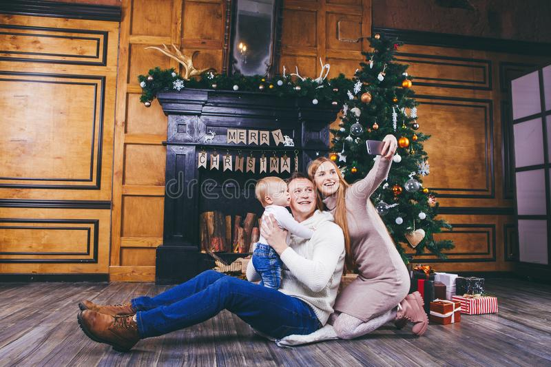 Christmas theme. young family with blond boy of one year sits on wooden floor against background of a Christmas tree with gifts an. D makes selfie, self-portrait royalty free stock photo