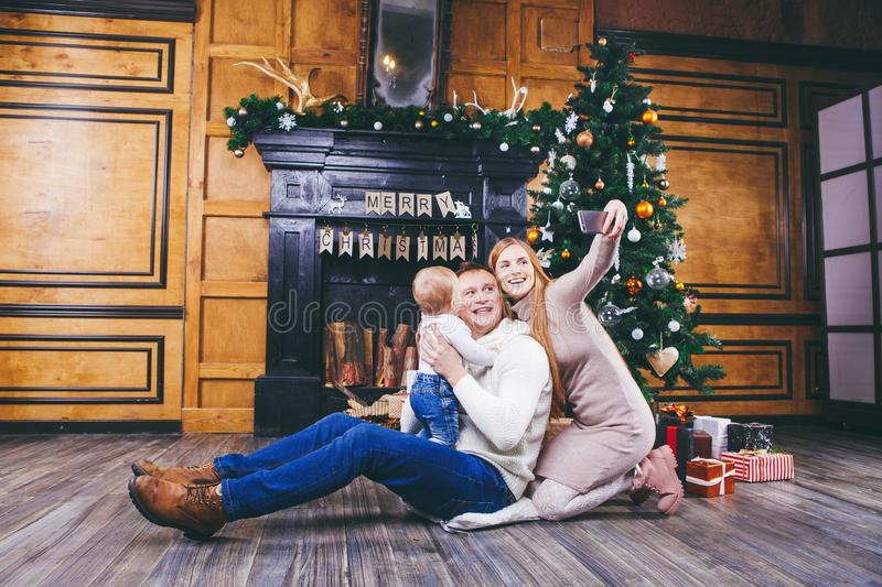 Christmas theme. young family with blond boy of one year sits on wooden floor against background of a Christmas tree with gifts an. D makes selfie, self-portrait royalty free stock images