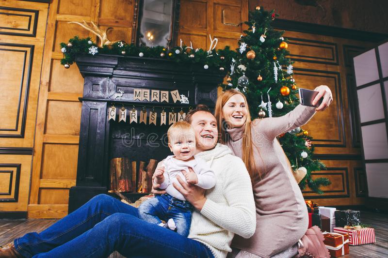 Christmas theme. young family with blond boy of one year sits on wooden floor against background of a Christmas tree with gifts an. D makes selfie, self-portrait royalty free stock image