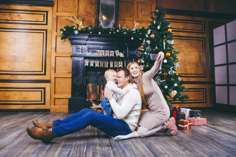 Christmas theme. young family with blond boy of one year sits on wooden floor against background of a Christmas tree with gifts an. D makes selfie, self-portrait stock photos