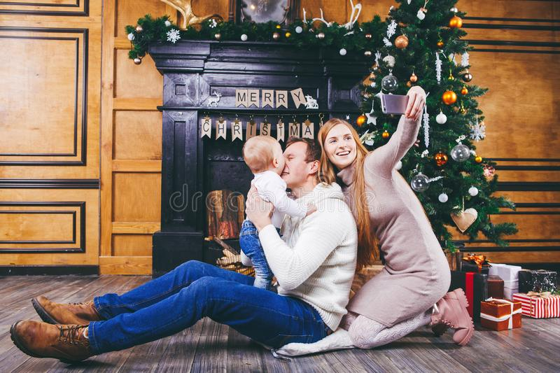 Christmas theme. young family with blond boy of one year sits on wooden floor against background of a Christmas tree with gifts an. D makes selfie, self-portrait stock photo