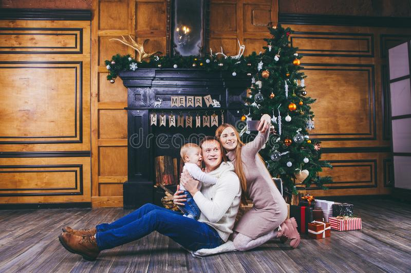 Christmas theme. young family with blond boy of one year sits on wooden floor against background of a Christmas tree with gifts an. D makes selfie, self-portrait royalty free stock photos