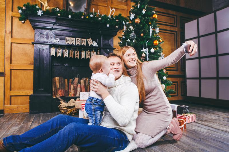 Christmas theme. young family with blond boy of one year sits on wooden floor against background of a Christmas tree with gifts an royalty free stock image