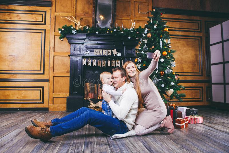 Christmas theme. young family with blond boy of one year sits on wooden floor against background of a Christmas tree with gifts an. D makes selfie, self-portrait stock images