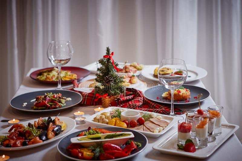 Christmas themed dinner table with a variety of appetizers and salads royalty free stock image