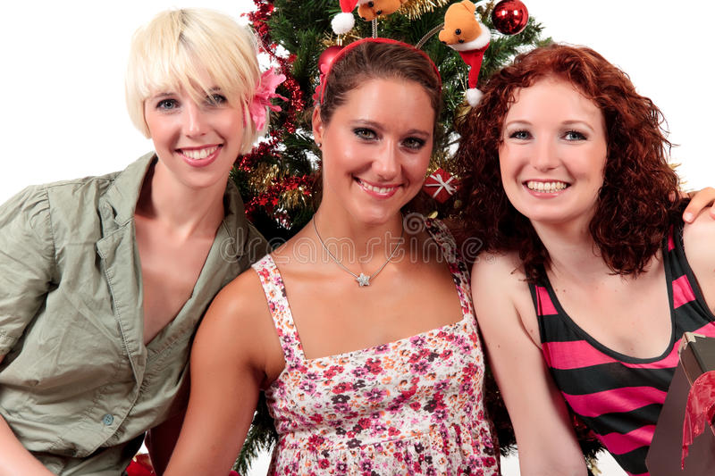 Christmas for three young attractive women. Three young attractive women hugging themselves near the Christmas tree. Studio shot. White background stock image