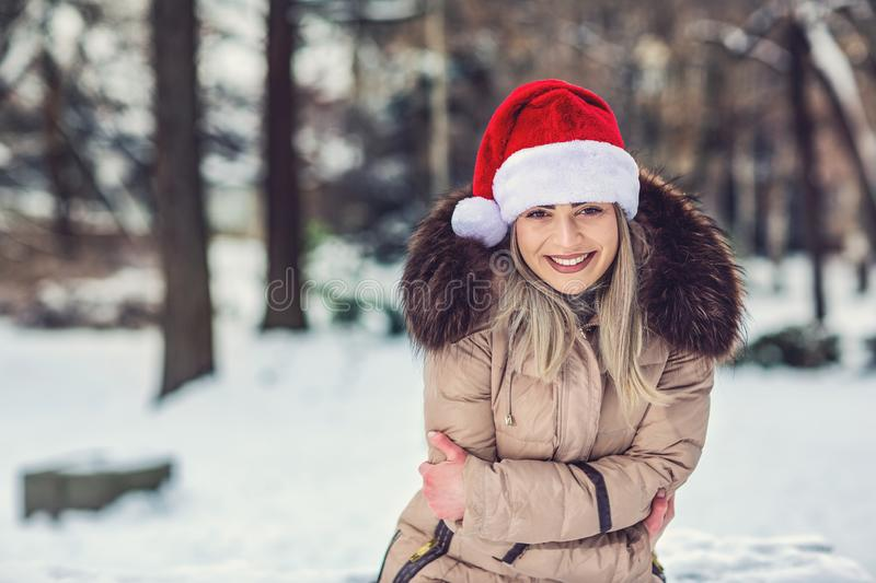 Christmas time – portrait of smiling woman with Santa hat winter snow day. stock photo