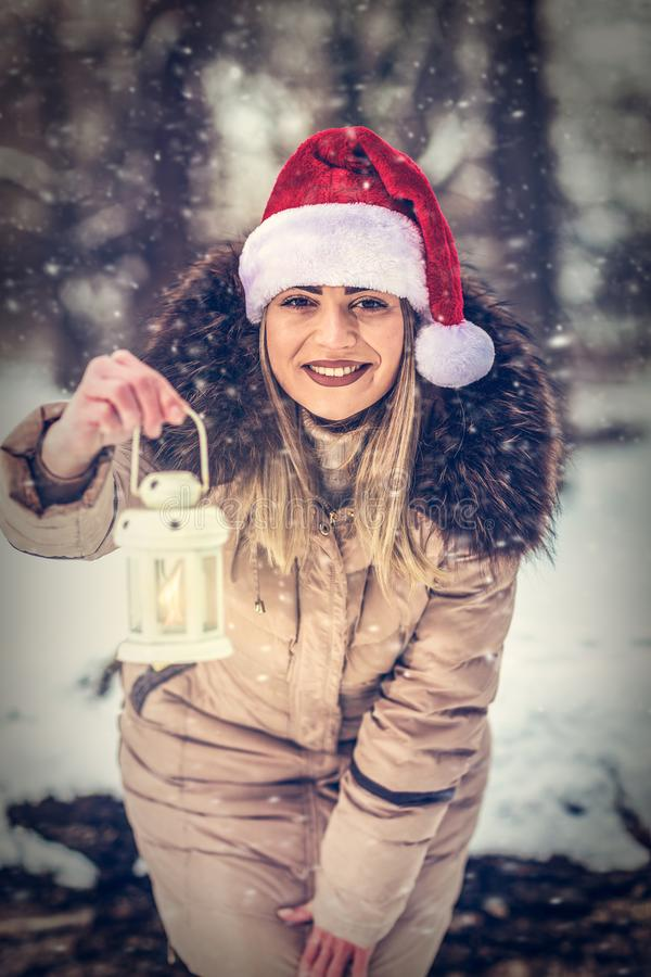 Christmas time – Smiling woman in Santa hat holding Christmas royalty free stock image