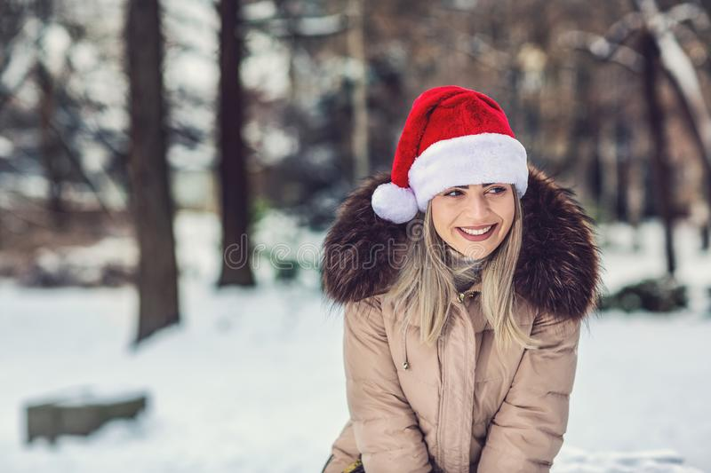 Christmas time – smiling woman with Santa hat winter snow day royalty free stock photography