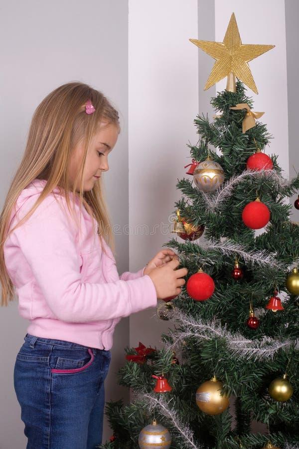 Christmas time. Little girl decorating Christmas tree royalty free stock photo