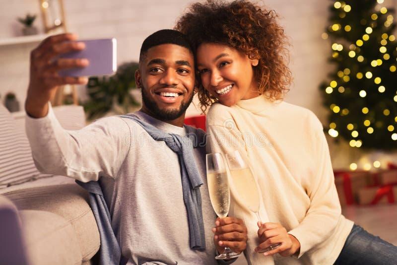 Christmas time. Afro couple taking selfie against xmas tree royalty free stock photo