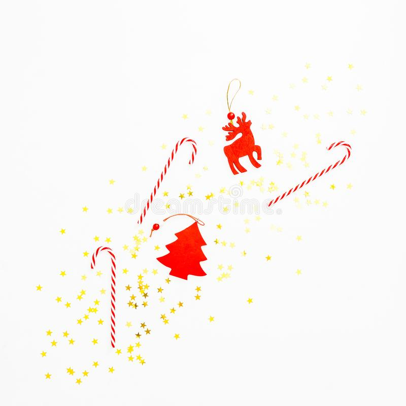 Christmas time composition with candy cane, toys and golden confetti on white background. Flat lay, top view. New year concept royalty free stock photo