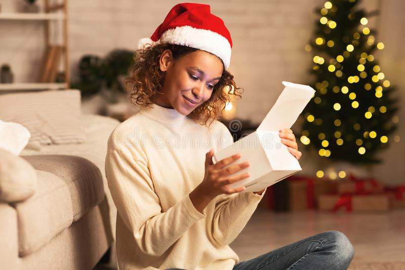 Christmas time. Cute afro girl looking inside gift box stock images