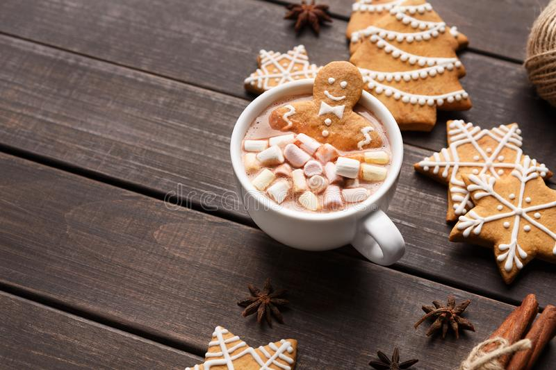Gingerbread man in cup of cocoa with marshmallows. Christmas time. Gingerbread man in cup of cocoa with marshmallows and sweets on wooden table, copy space royalty free stock photography