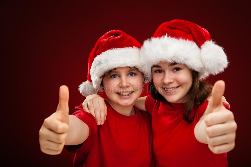 Christmas time - girl and boy with Santa Claus Hat showing OK sign. Christmas time - girl and boy in Santa Claus Hats showing OK sign royalty free stock photos