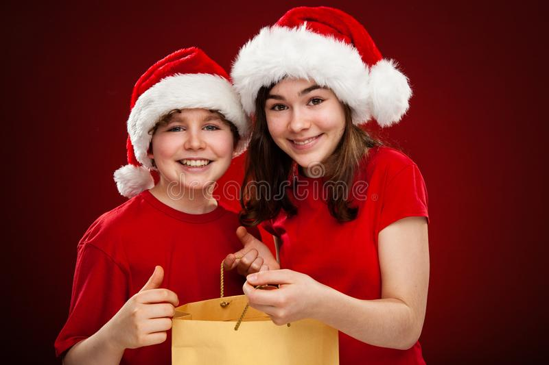 Christmas time - girl and boy with Santa Claus Hats. Christmas time - girl and boy in Santa Claus Hats royalty free stock photos
