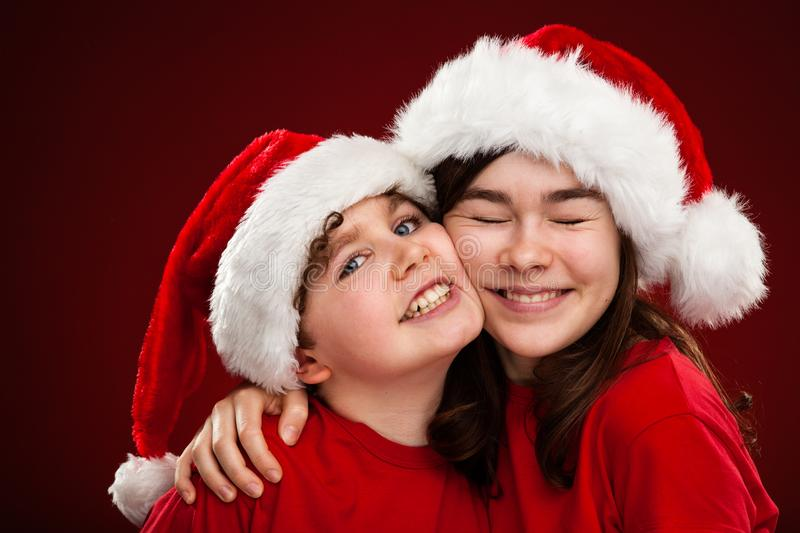 Christmas time - girl and boy with Santa Claus Hats. Christmas time - girl and boy in Santa Claus Hats royalty free stock images