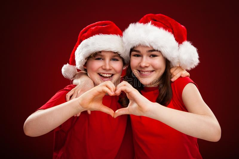 Christmas time - girl and boy with Santa Claus Hats showing heart sign. Christmas time - girl and boy in Santa Claus Hats showing heart sign stock image