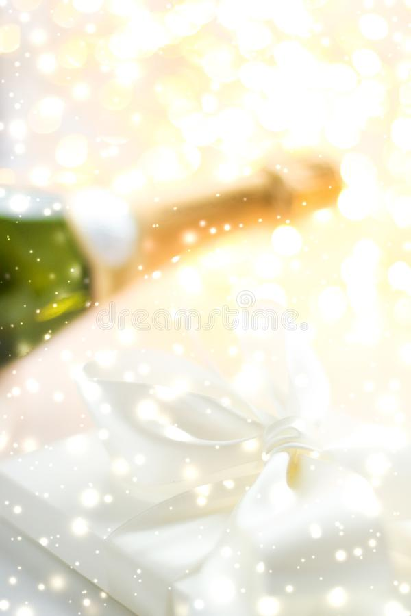 New Years Eve holiday champagne bottle and a gift box and shiny snow on marble background. Christmas time, happy holidays and luxury present concept - New Years stock image