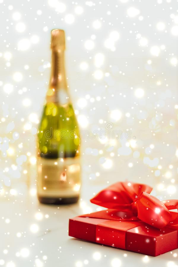 New Years Eve holiday champagne bottle and a gift box and shiny snow on marble background. Christmas time, happy holidays and luxury present concept - New Years stock photo