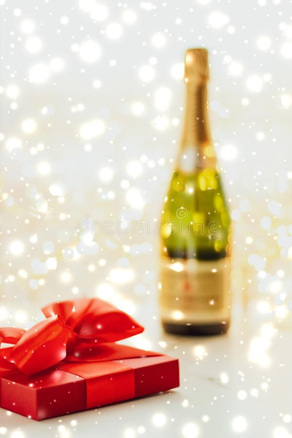 New Years Eve holiday champagne bottle and a gift box and shiny snow on marble background. Christmas time, happy holidays and luxury present concept - New Years stock photography